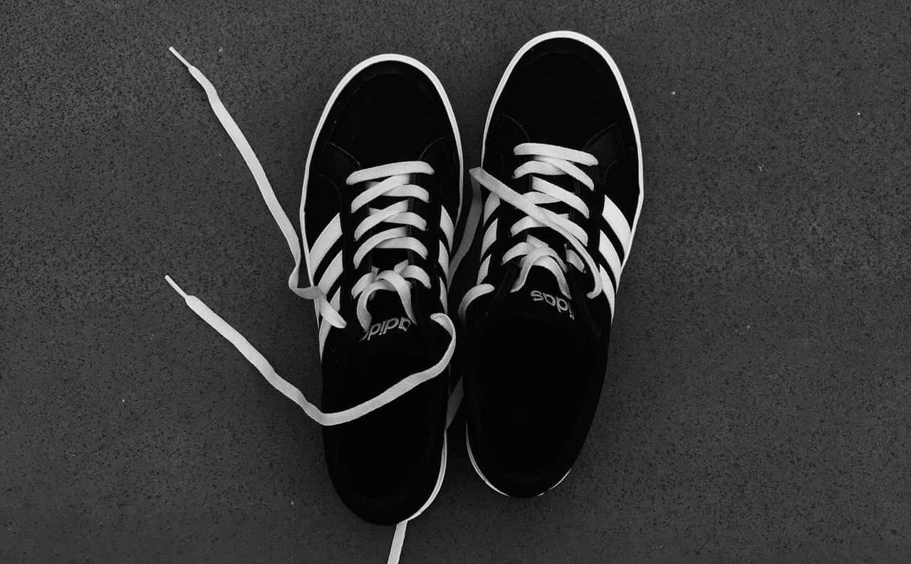 Black and white sneakers against a gray background.