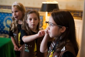 Three Girl Scouts listening intently to a STEM presentation. One is wearing GoogleGlass.