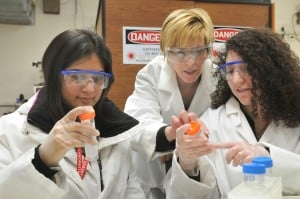 3 women wearing laboratory dress and eye protection.