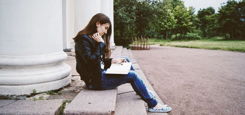 A student sitting and reading a book.