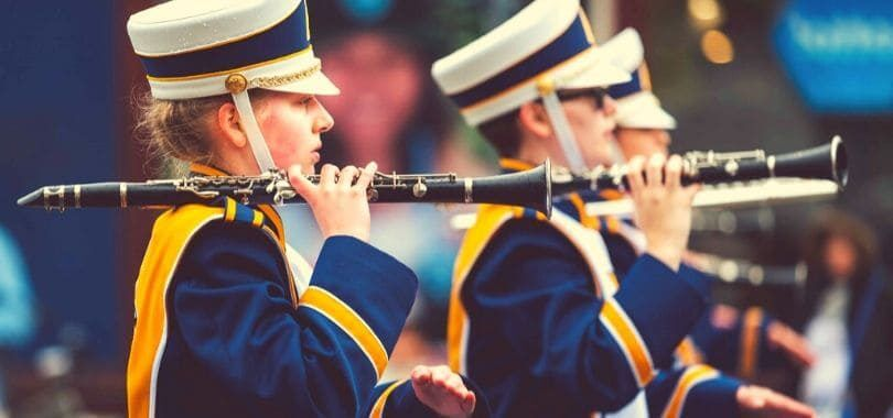 Students in a marching band lined up, holding their instruments.