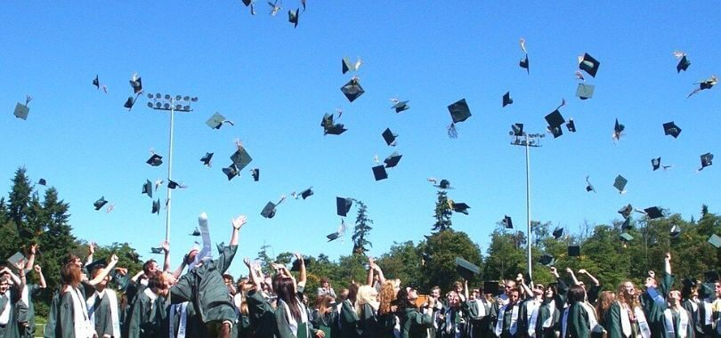 College students throwing their graduation caps in the air.
