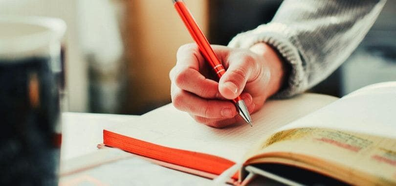 A student writing in a notebook with an orange pen.