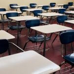 Rows of beige desks and blue chairs in a high school.