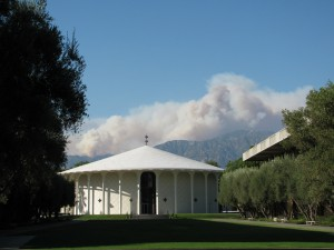 White chapel building on the CalTech campus with a backdrop of mountains.