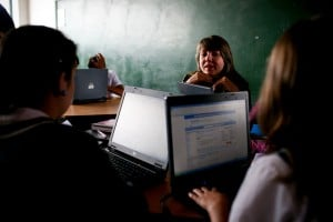 A teacher guiding her students in a technical education class using their laptops.