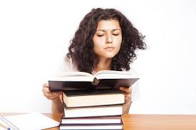 A college girl reads a book in the library.