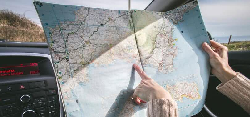 A person holding and pointing at a paper map.