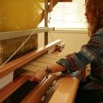 A lady knitting fabric using a manual machine.