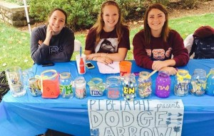 Pi Beta Phi sorority sisters at a table with colorful donoation jars and banner.