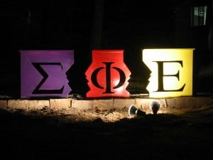 The Sigma Phi Epsilon letters on colorful boxes, illuminated by a spotlight.
