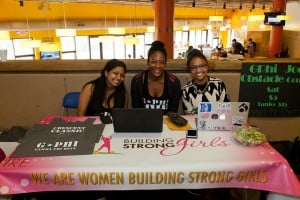 """Gamma Phi Beta sisters sitting with a banner that says """"We are women building strong girls."""""""