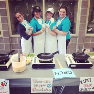 Alpha Omicron Pi sisters holding a spatula ready to cook omelette breakfast.