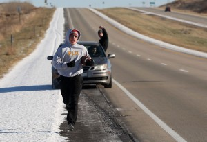 A college student running while other students cheer him on in a car from behind.