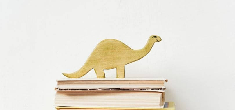 A wooden dinosaur on top of a stack of books.
