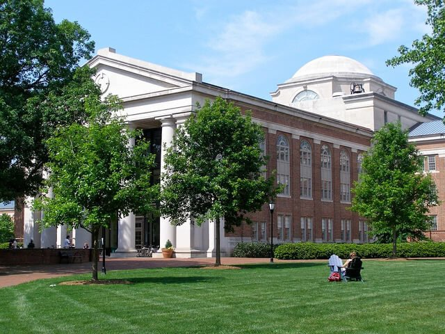 Student sitting on the lawn at the east side of Chambers in Davidson College.
