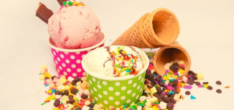 Ice cream in cups, with ice cream cones next to the cups.