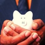 A person holding a white piggy bank in their hands.