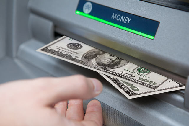 Photograph of a person withdrawing money from an ATM.