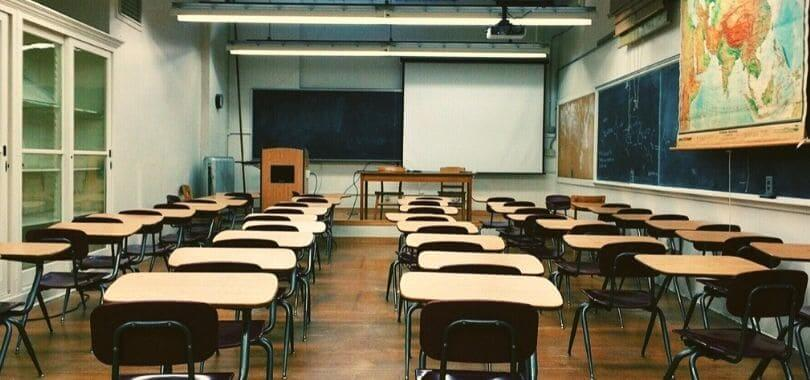 An empty classroom with a blackboard, as well as beige and brown desks.