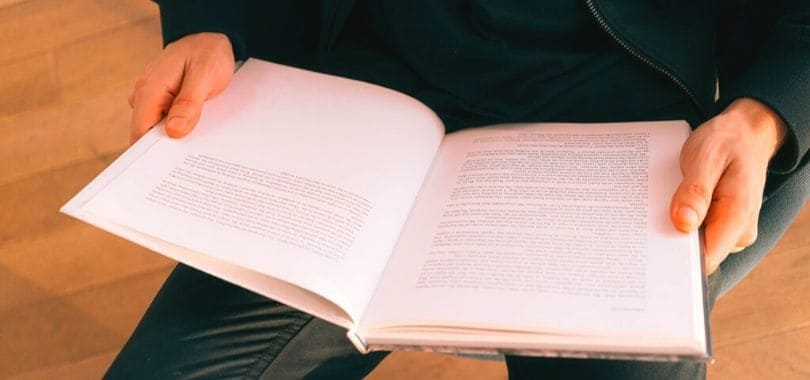 A student holding a textbook open.