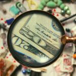 A magnifying glass pointed towards many items, with twenty dollar bills magnified.