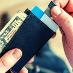 A student holding their wallet with a ten dollar bill sticking out of it.