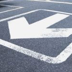 A white arrow pointing away printed on a road.
