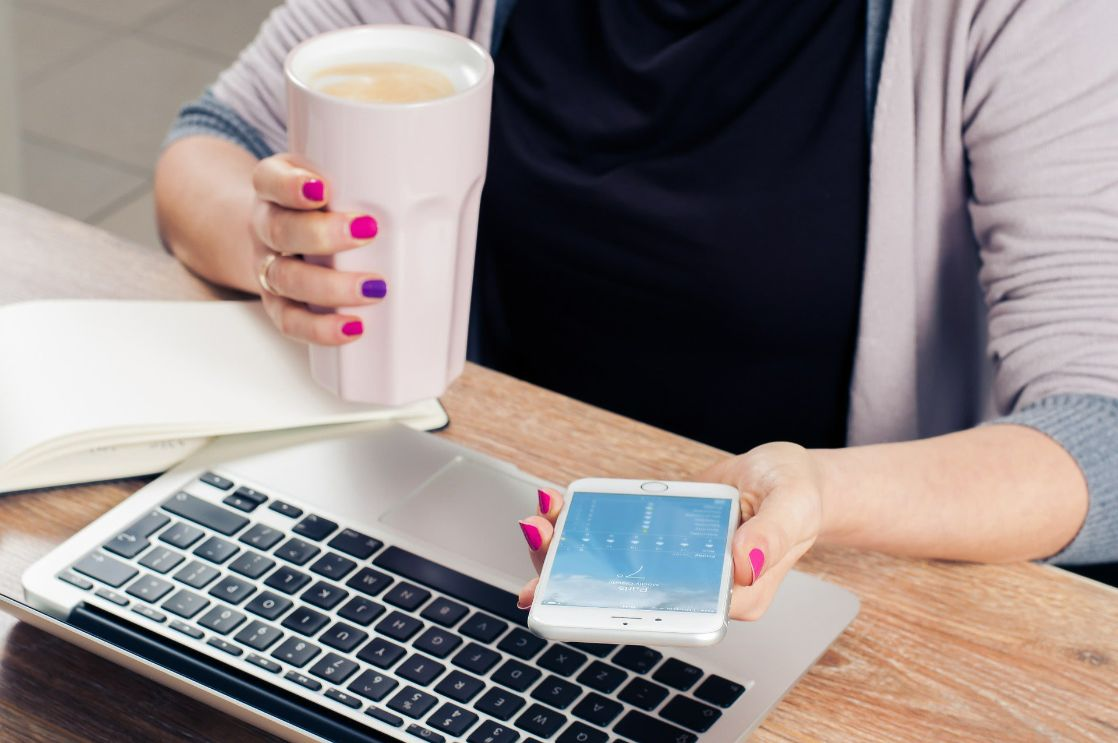 A student holding a phone in one hand and a cup of coffee in the other.