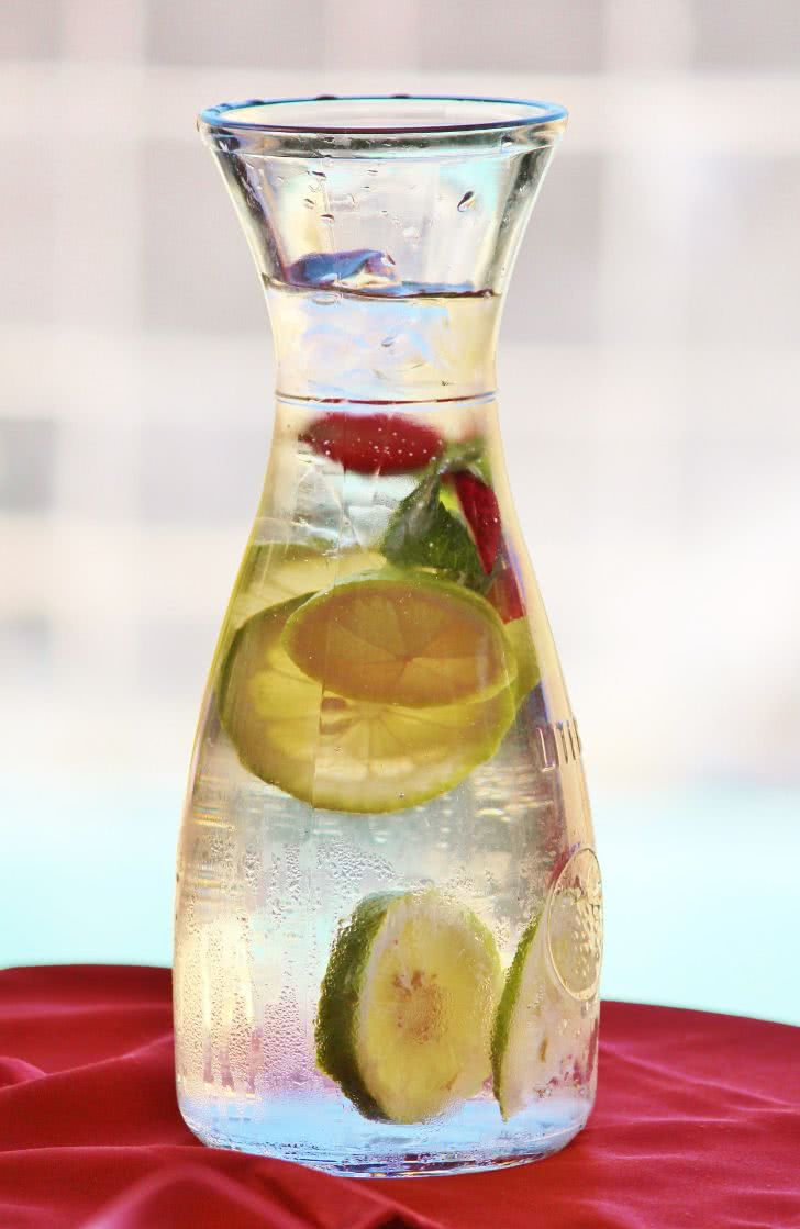 A pitcher filled with water with a slice of lemon inside.