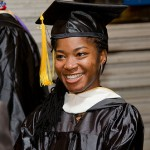 A girl graduate student is smiling and looking far away.
