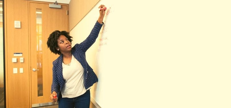 A person writing and talking up at a whiteboard.