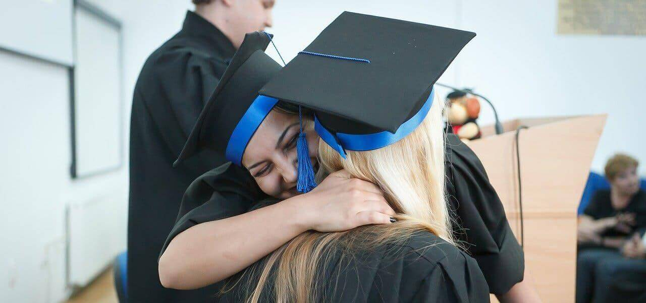 A graduating college student hugging another student.
