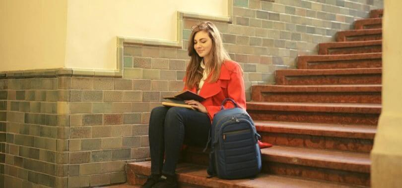 A student sitting on a staircase with a backpack next to them.