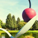 A sculpture of a cherry on top of a spoon.