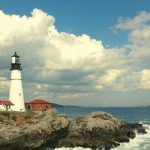 A lighthouse in Maine next to the ocean.