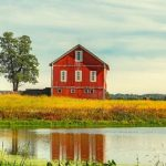 A red barn with a small pond in front of it.