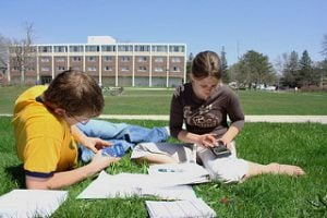 Two students studying outside on a blanket surrounded by books.