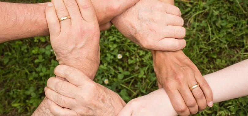 Multiple people's hand grabbing another person's wrist to form a ring.