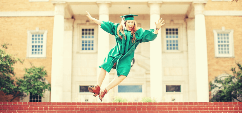 College student wearing a green graduation robe jumping.