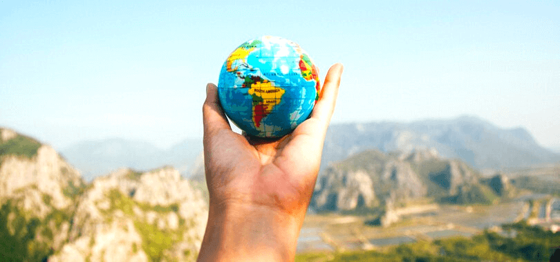 A student holding a small globe with mountains in the background.