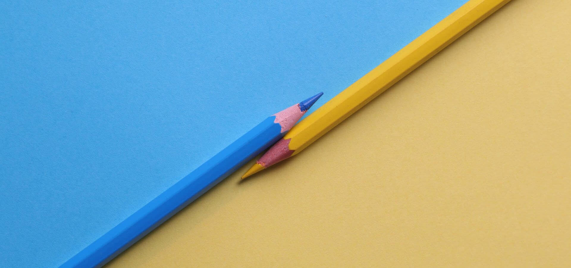 Blue and beige color pencils laying parallel to each other.