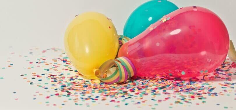 Colorful balloons laying together on top of confetti.