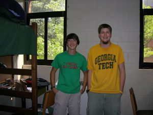 Two college students standing and smiling for picture taken inside their dorm room.