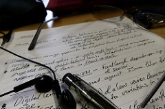 Earbuds, pen, and eyeglass sitting atop college notes.