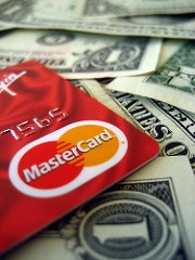 Red MasterCard with dollar bills in the background.