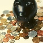 A piggy bank standing on top of a pile of coins.