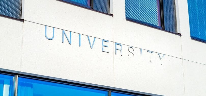 """A """"university"""" sign on the side of a building."""