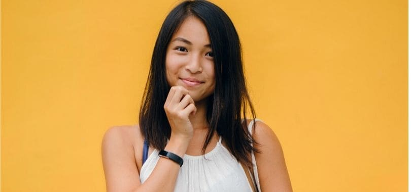 An Asian American student standing against an orange background.