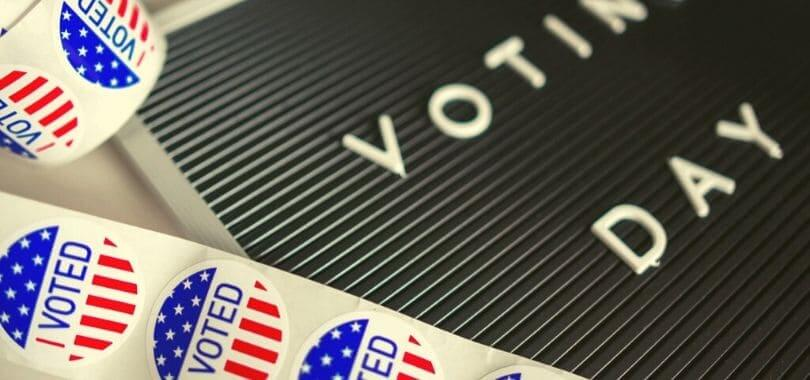 """""""I voted"""" stickers next to a board that says """"voting day."""""""